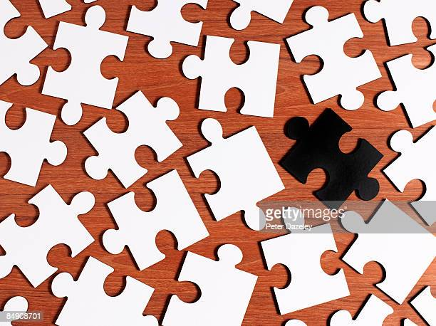 Blank white jigsaw puzzle with black piece.