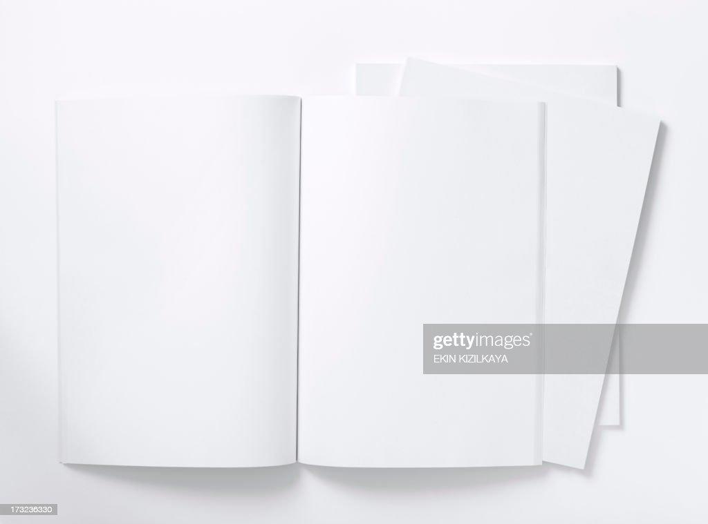 Blank white magazine lying open on a white table : Stock Photo