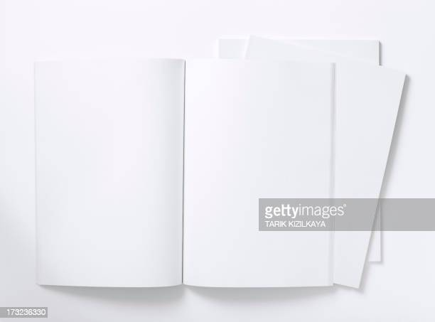 blank white magazine lying open on a white table - magazine page stock photos and pictures