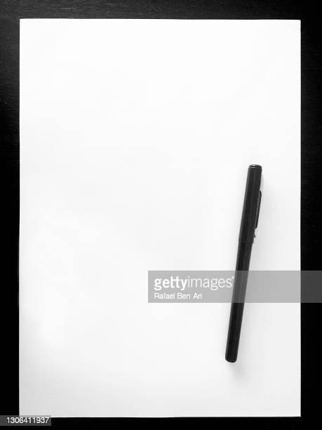 blank white paper and a black pen - rafael ben ari stockfoto's en -beelden