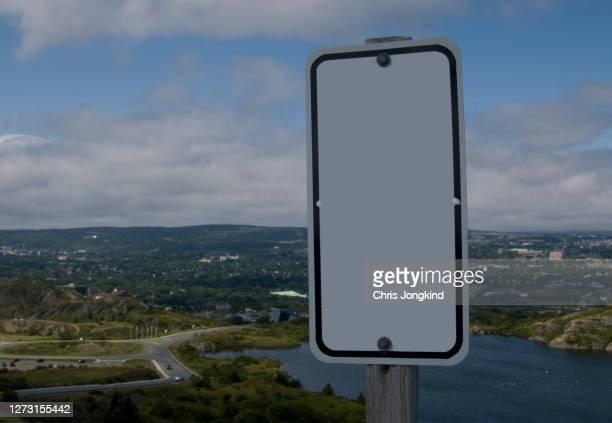 blank white sign over town in hilly landscape - paisajes de st johns fotografías e imágenes de stock