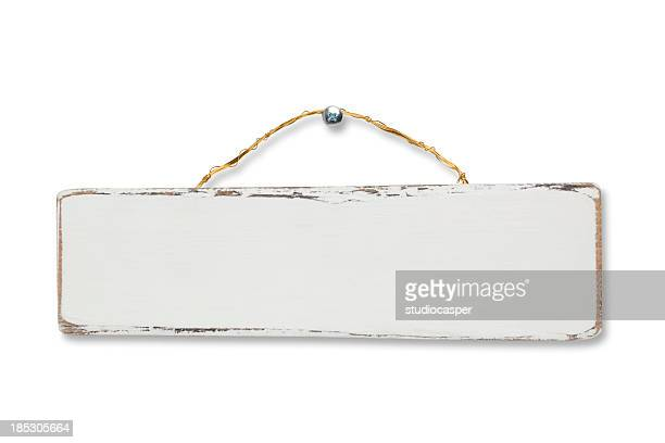 A blank white wooden sign nailed to a wall