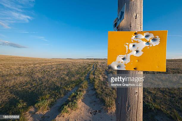 Blank yellow sign with bullet holes