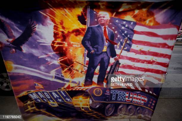 Blanket featuering the US president atop a tank and holding a gun hangs near the Huntington Center in Toledo, Ohio January 9, 2020 where he is...