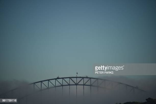 TOPSHOT A blanket of fog covers the Harbour Bridge and Opera House in Sydney on July 5 2018 Planes were delayed and ferries cancelled on July 5 as...