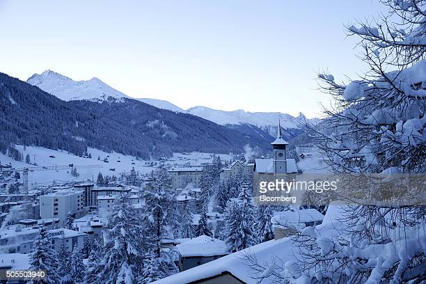 A blanket of snow covers the buildings and trees as the early morning light rises above the mountains in Davos Switzerland on Monday Jan 18 2016...
