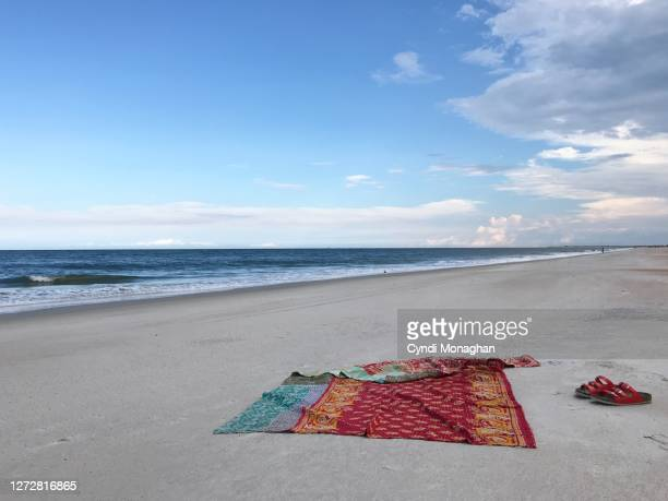 blanket spread out on a beautiful beach - picnic blanket stock pictures, royalty-free photos & images