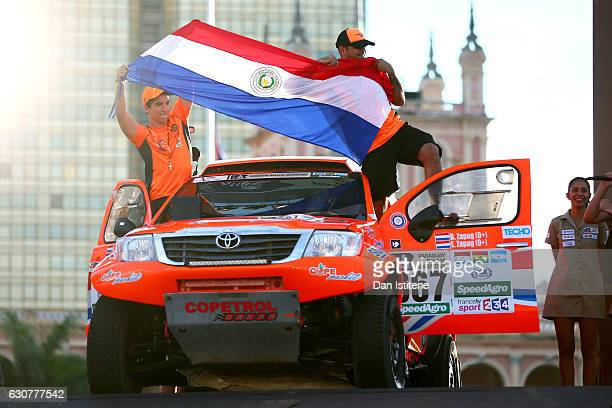 Blas Zapag of Paraguay and Toyota South Racing and co-driver Enrique Zapag of Paraguay hold their national flag as they stand on their Hilux Toyota...