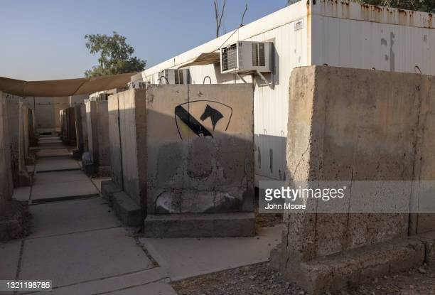 Blast wall, partially painted with a U.S. Army First Cavalry Division insignia protects living quarters for military personnel and contractors at a...