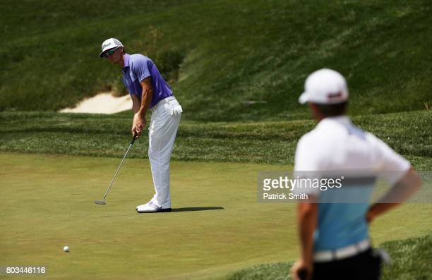 Blayne Barber of the United States putts as Matt Jones of Australia looks on on the 17th green during the first round of the Quicken Loans National...