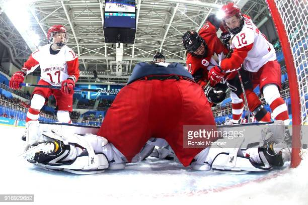 Blayre Turnbull of Canada fights for the puck against Yekaterina Lobova of Olympic Athlete from Russia during the Women's Ice Hockey Preliminary...