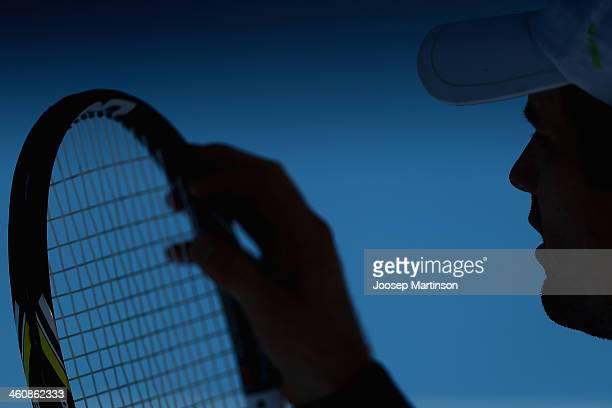 Blaz Kavcic of Slovenia plays adjusts his racquet strings in his qualifying match against Albert Ramos of Spain during day two of the Sydney...
