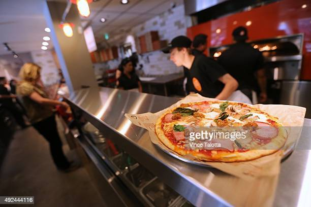 Blaze Pizza employees making customized pizza for customers at the Build Your Own Pizza counter at Blaze Pizza on Dundas St E at Yonge Street in...