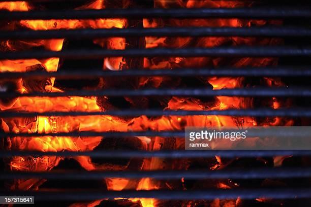 Blazing hot coals behind a steel grate