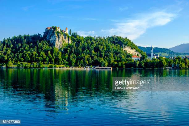 Bled Castle Blejski grad located on a rocky mountain seen across Lake Bled Blejsko jezero