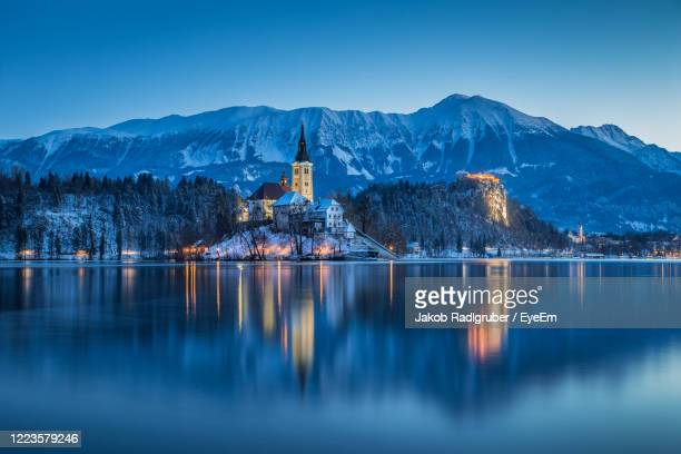 bled castle in lake by mountains at dusk - スロベニア ストックフォトと画像