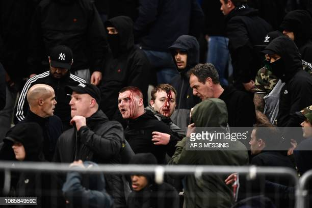 TOPSHOT Bleeding Ajax fans react after clashes with Greek riot police prior to the start of the UEFA Champions League football match between AEK...
