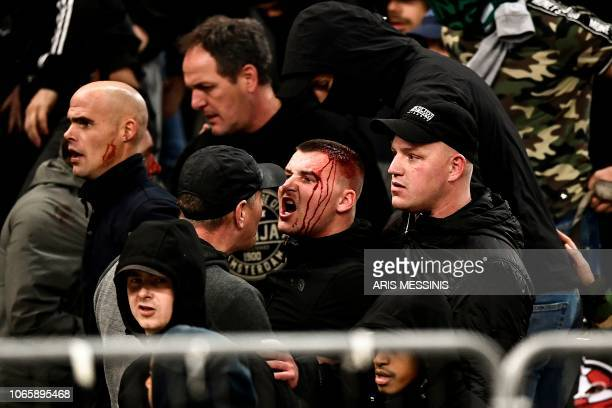 TOPSHOT Bleeding Ajax fans react after clashes with the Greek riot police prior to the start of the UEFA Champions League football match between AEK...