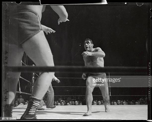 Bleeding Antonio Rocca hurls himself in a rage at the outstretched arms of Lord Leslie Carlton during their wrestling match at the Garden tonight...