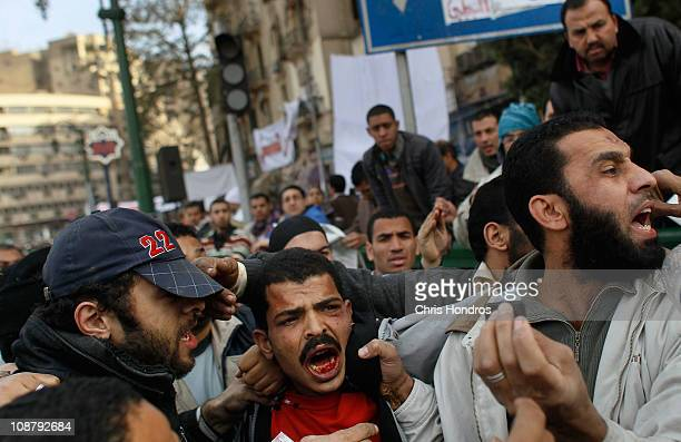 A bleeding captured Egyptian man suspected of being in the government security forces is roughly moved by antigovernment protesters in Tahrir Square...