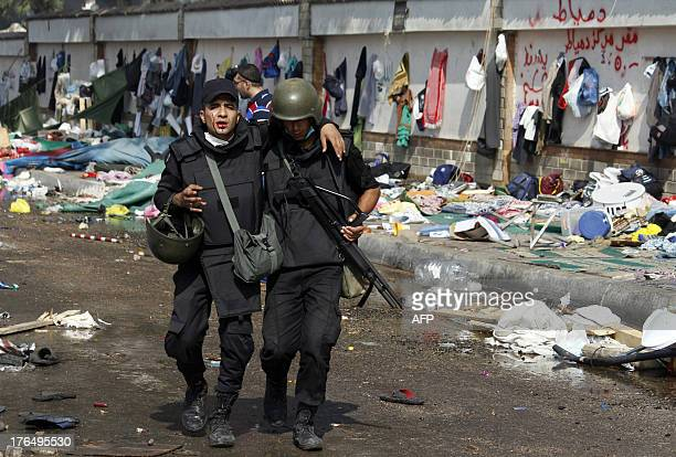 Bleeding Egyptian riot policeman walks with the help of a comrade during clashes that broke out as security forces moved in to disperse supporters of...