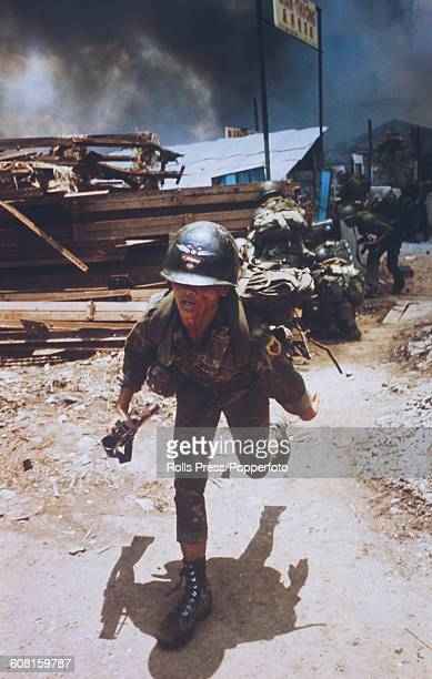 Bleeding from a facial wound a South Vietnamese ARVN Ranger runs for cover in a wood yard as a fire rages amongst buildings behind during fighting in...