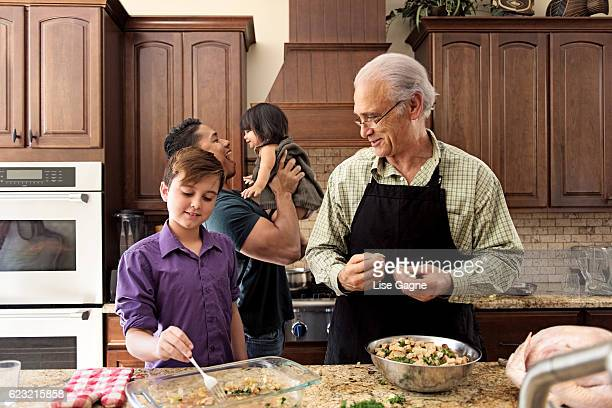blended family preparing thanksgiving dinner together - stepfamily stock photos and pictures