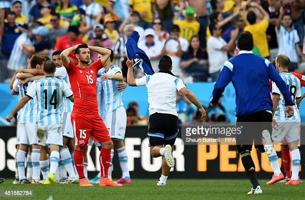 Blerim Dzemaili of Switzerland reacts while Argentina players celebrate after the 2014 FIFA World Cup Brazil Round of 16 match between Argentina and...