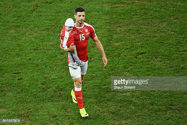 Blerim Dzemaili of Switzerland with his child leaves the pitch after the UEFA EURO 2016 Group A match between Switzerland and France at Stade...