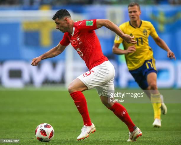 Blerim Dzemaili of the Switzerland national football team and Viktor Claesson of the Sweden national football team vie for the ball during the 2018...