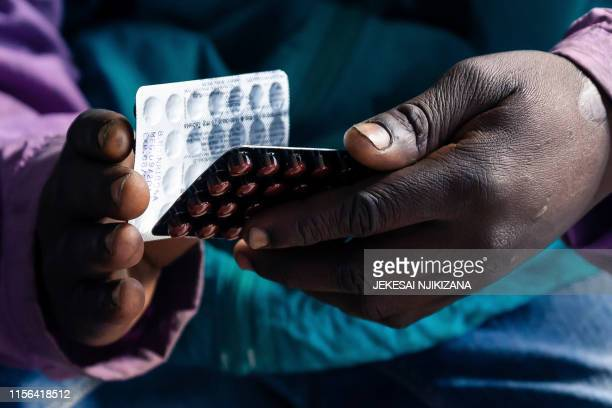 Blessing Chingwaru an HIV positive TB patient holds a packet of tablets received as part of his treatment at Rutsanana Polyclinic in Glen Norah...