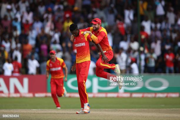 Blessing Muzarabani and Sean Ervine of Zimbabwe celebrate the wicket of Ahmed Raza of the UAE during The ICC Cricket World Cup Qualifier between the...