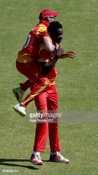 Blessing Muzarabani of Zimbabwe celebrates with Graeme Cremer after taking the wicket of Nasir Jamal of Afghanistan during the ICC Cricket World Cup...