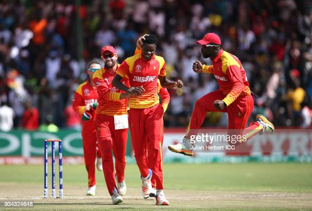 Blessing Muzarabani of Zimbabwe is congratulated by team mates after taking the wicket of Chris Gayle of The West Indies during The Cricket World Cup...