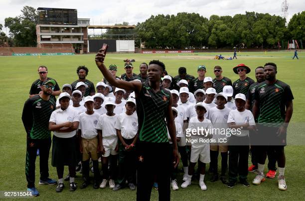 Blessing Muzarabani of Zimbabwe takes a selfie of players and local school children during a 'Cricket for Good' session at Queens Sports Club on...