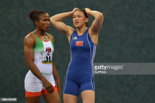 Blessing Oborududu of Nigeria walks by a disappointed Hafize Sahin of Turkey after winning against in the Women's Freestyle 63kg Wrestling final...