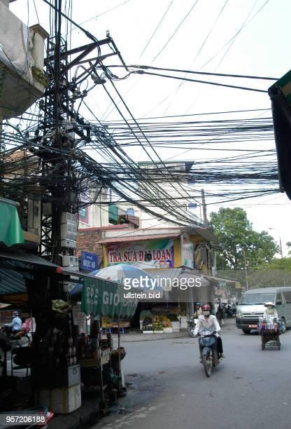 Blick auf ein wahres Gewirr von Stromkabeln an einer Straßenkreuzung in der Altstadt von Hanoi der Hauptstadt der Sozialistischen Republik Vietnam...