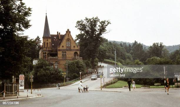 Blick über eine Straßenkreuzung in Eisenach zur heutigen Wartburgallee der Zufahrt zur Wartburg aufgenommen 1969 Am Straßenrand prangt ein Aufsteller...