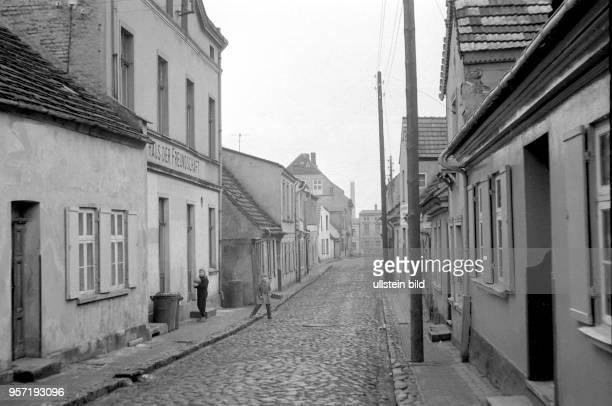 Blick in eine Straße mit Kopfsteinpflaster und grauen tristen kleinen Häusern in der Stadt Wolgast an der Ostseeküste zur Insel Usedom, aufgenommen...
