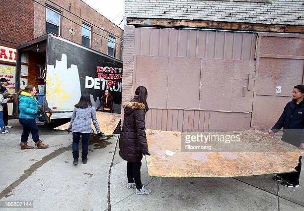 Blight Busters volunteers carry sheets of plywood while volunteers help clean up a section of Detroit Michigan US on Saturday March 23 2013 Motor...