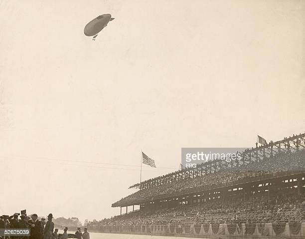 A blimp flies over Sheepshead Bay Speedway as spectators watch and talk amongst themselves Brooklyn New York late 1910s The Speedway an auto racing...