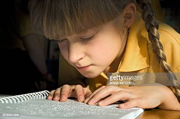 blind 9 year old girl reading a braille book - braille stock pictures, royalty-free photos & images