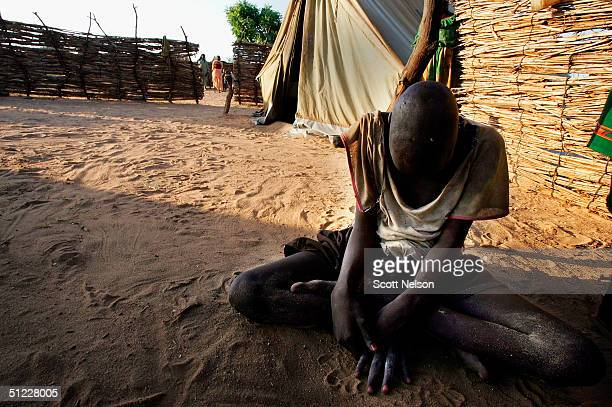 A blind and mentally handicapped Sudanese refugee boy who recently fled with his family from conflict in the Dafur region of Sudan sits in a corner...