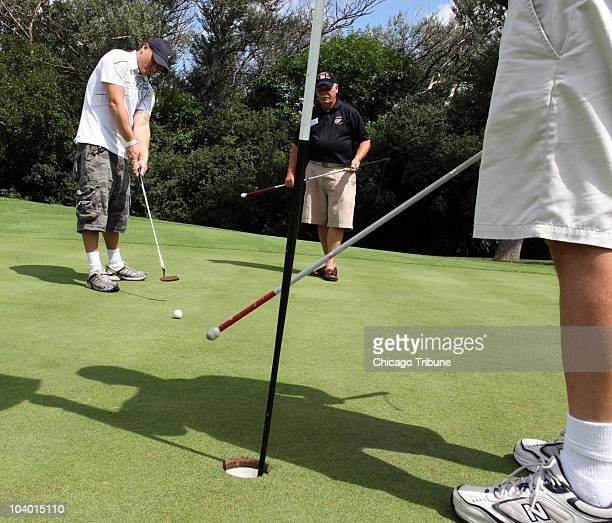 Blind Army Veteran Alexander PerezVargas with volunteer Don Kenyon listens to another volunteer tap on the flag to pinpoint his putt at the Willow...