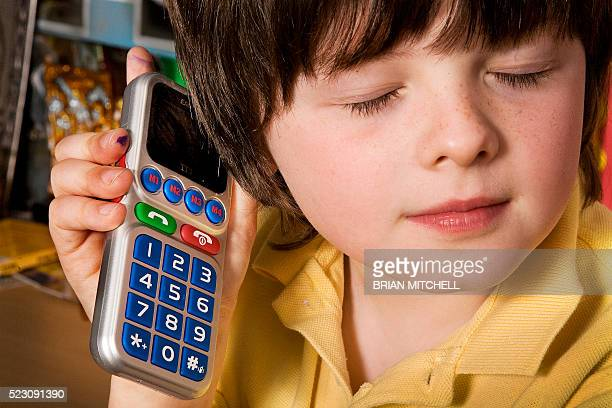 blind boy aged 7 using a special large button braille touch mobile cell phone for the visualy impared - assistive technology stock pictures, royalty-free photos & images