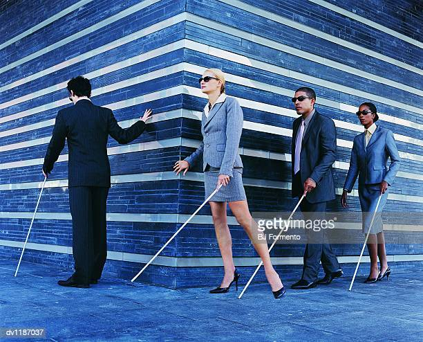 Blind Businessmen and Businesswomen Walking in a Line Holding Walking Sticks