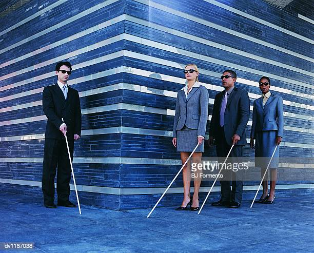 Blind Businessmen and Businesswomen Walking in a Line Holding White Sticks