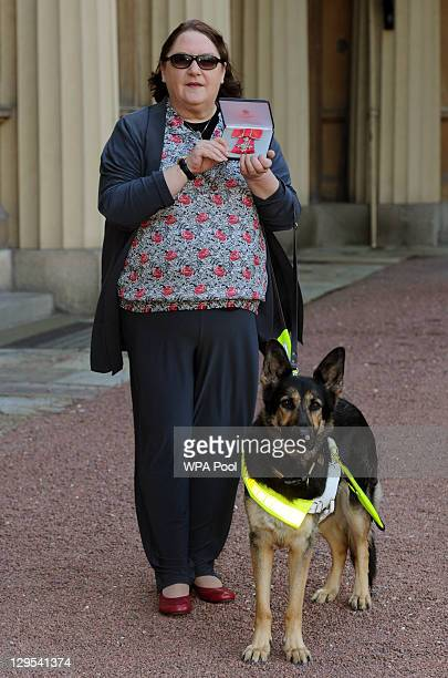 Blind composer Jacqueline Clifton her guide dog Henna pose after she received her MBE medal from the Princess Anne Princess Royal at an Investiture...
