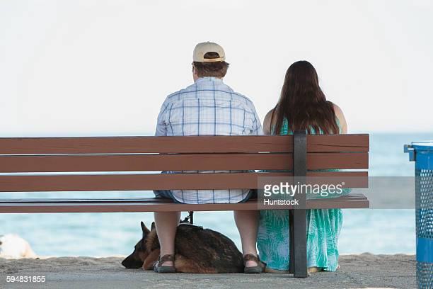 Blind couple sitting on a bench at the beach with their service dog