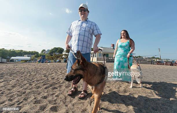 Blind couple with their service dogs walking along the beach